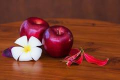Maçãs vermelhas com flor e folhas na tabela marrom de madeira Fotografia de Stock