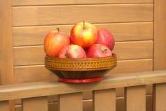 Maçãs vermelhas e amarelas maduras no close up de madeira da bacia Foto de Stock Royalty Free