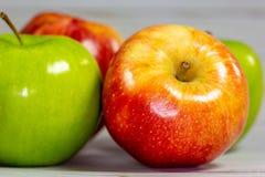 Maçãs vermelhas e verdes que esperam para ser comido na mesa de cozinha imagens de stock