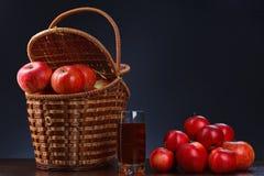 Maçãs vermelhas em um suco da cesta e da maçã imagens de stock