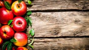 Maçãs vermelhas frescas com as folhas verdes na tabela de madeira Fotografia de Stock