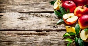 Maçãs vermelhas frescas com as folhas verdes na tabela de madeira Foto de Stock Royalty Free