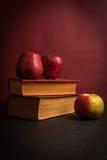 Maçãs vermelhas frescas e livros velhos imagens de stock