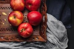 Maçãs vermelhas frescas na bandeja de madeira sobre o corredor azul da tabela Imagens de Stock