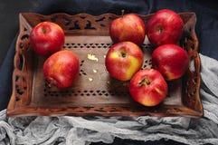 Maçãs vermelhas frescas na bandeja de madeira sobre o corredor azul da tabela Fotografia de Stock
