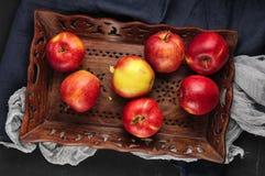 Maçãs vermelhas frescas na bandeja de madeira sobre o corredor azul da tabela Imagem de Stock Royalty Free