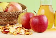 Maçãs vermelhas, maçãs secadas e sidra de maçã fresca no fundo de madeira Foto de Stock Royalty Free