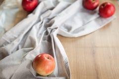 Maçãs vermelhas maduras no guardanapo cinzento imagens de stock