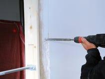 Maçon faisant un dégagement pour les conduits électriques pendant la rénovation de la maison photos libres de droits