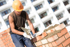 Maçon installant des briques avec l'outil de truelle Photographie stock