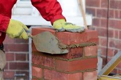 Maçonnerie - pose d'une brique photo stock