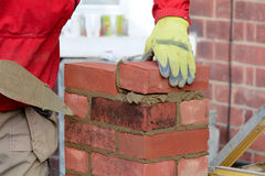 Maçonnerie - pose d'une brique photo libre de droits