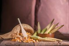 Maíz de semilla y maíz de bebé en fondo de madera de la tabla Fotografía de archivo libre de regalías