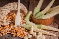 Maíz de semilla y maíz de bebé en fondo de madera de la tabla Fotos de archivo