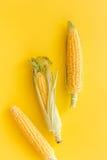Maíz en mazorcas en copyspace amarillo de la opinión superior del fondo Imagen de archivo libre de regalías