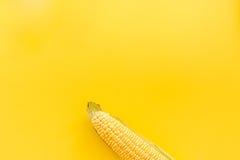 Maíz en mazorcas en copyspace amarillo de la opinión superior del fondo Foto de archivo