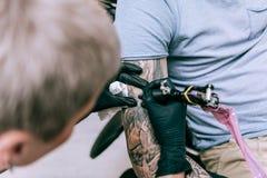 Maître attentif précis finissant et améliorant le tatouage géant photographie stock
