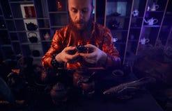 Maître caucasien dans le kimono faisant le thé naturel dans la chambre noire avec un intérieur en bois Tradition, santé, harmonie photos stock