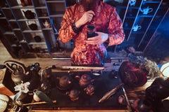 Maître caucasien dans le kimono faisant le thé naturel dans la chambre noire avec un intérieur en bois Tradition, santé, harmonie photos libres de droits