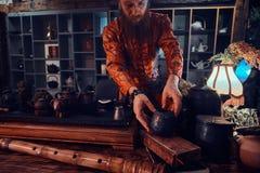 Maître caucasien dans le kimono faisant le thé naturel dans la chambre noire avec un intérieur en bois Tradition, santé, harmonie image libre de droits