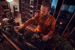 Maître caucasien dans le kimono faisant le thé naturel dans la chambre noire avec un intérieur en bois Tradition, santé, harmonie image stock