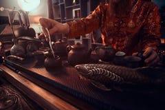 Maître caucasien dans le kimono faisant le thé naturel dans la chambre noire avec un intérieur en bois Tradition, santé, harmonie photographie stock libre de droits