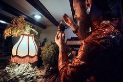 Maître caucasien dans le kimono faisant le thé naturel dans la chambre noire avec un intérieur en bois Tradition, santé, harmonie photo stock