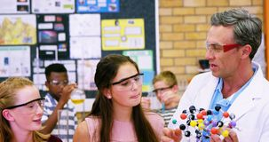 Maître d'école aidant des écoliers sur le modèle 4k de molécule banque de vidéos