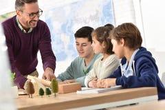 Maître d'école avec des élèves dans la classe de la science image stock