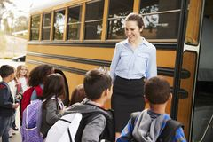 Maître d'école disposant des enfants à monter dans l'autobus scolaire images stock
