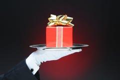 Maître d'hôtel avec le cadeau sur le plateau Image libre de droits