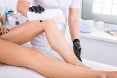 Maître dans le dépilage utilisant les cosmétiques professionnels pour le dépilage photos libres de droits