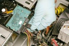 maître dans les gants bleus Elle a obtenu l'unité de disque dur à partir de l'ordinateur Profondeur de coupe là modifie la tonali photos stock