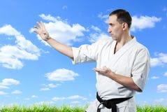 Maître de karaté dans le kimono sur le ciel bleu Photographie stock