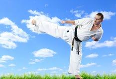 Maître de karaté dans le kimono sur le ciel bleu Photos stock