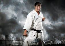 Maître de karaté dans le kimono sur le ciel orageux Image stock