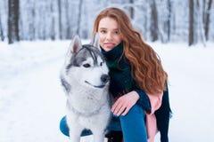 Maître femelle sur la formation de chien avec le chien de traîneau sibérien Image libre de droits