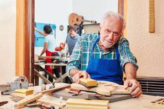 Maître luthier supérieur avec le papier à l'émeri Images stock