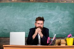 Maître mûr barbu de professeur écoutant avec l'attention Le tenue de soirée de professeur se reposent au tableau de salle de clas photos libres de droits