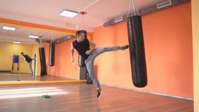 Maître masculin caucasien des sports en arts martiaux, donnant un coup de pied un sac de sable dans le gymnase, formation d'autod clips vidéos