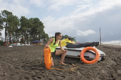 Maître nageur de fille en service gardant une balise à la plage Arrosez le scooter, outil orange de conservateur de matériel de s photographie stock libre de droits