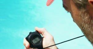 Maître nageur regardant le chronomètre le côté de piscine banque de vidéos