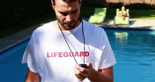 Maître nageur regardant le chronomètre près du poolside clips vidéos