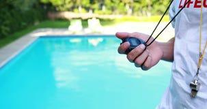 Maître nageur regardant le chronomètre près du poolside banque de vidéos