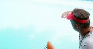 Maître nageur se tenant sur le côté de piscine banque de vidéos