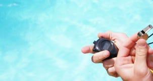 Maître nageur tenant le chronomètre et siffler banque de vidéos