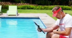 Maître nageur tenant le presse-papiers et regardant le chronomètre clips vidéos