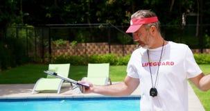 Maître nageur tenant le presse-papiers et siffler clips vidéos