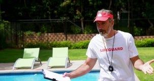 Maître nageur tenant le presse-papiers et siffler banque de vidéos
