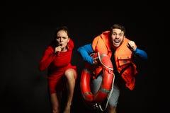 Maître nageurs dans le gilet de vie avec siffler de balise d'anneau Photographie stock libre de droits